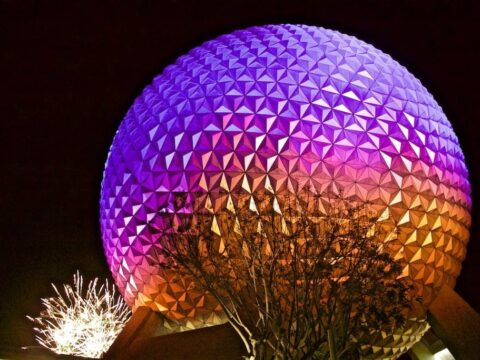 Spaceship Earth lit up in red, orange and purple at night
