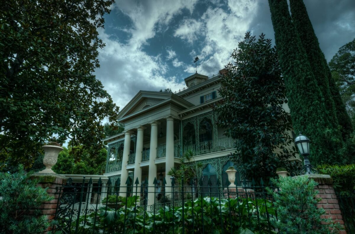 Dark sky, Large White Building Surrounded by Greenery Outside Disney's Haunted Mansion Attraction
