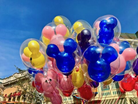 Blue, Pink, and Yellow Mickey Shaped Balloons outside in Daytime