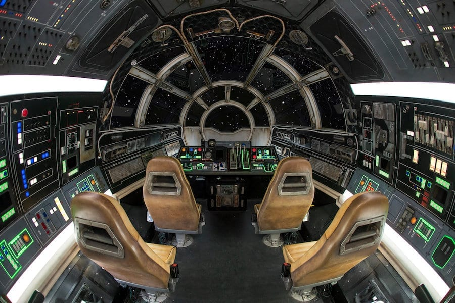 Inside of the Millennium Falcon, four brown captain's chairs, green and red control pannel, greys and blacks as interior