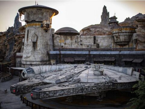 Grey and brown cement buildings in front of rock structures featuring the millennium falcon