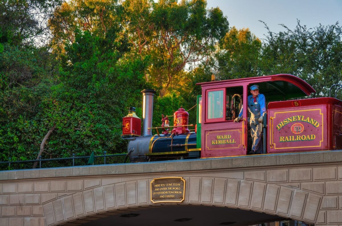 Red Disneyland Railroad with Train Conductor Standing on Train, Green trees in Background