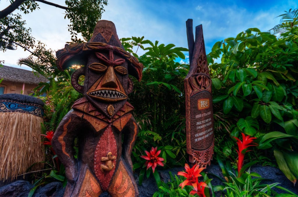 Tropical leaves and greenery with brown Tiki statue