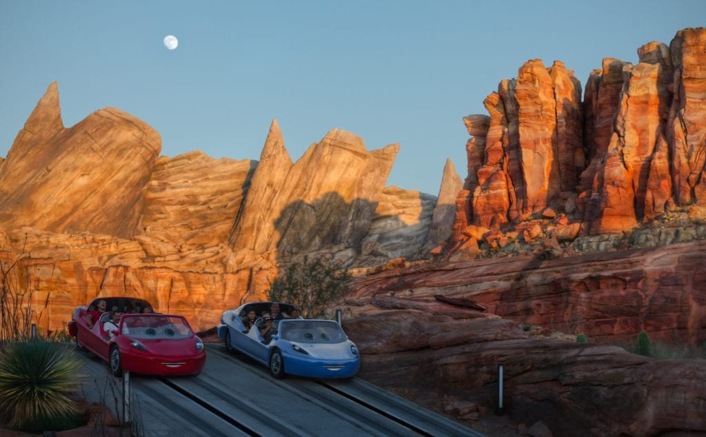 Lightning McQueen and Sally Carrera Riding In Front of Red and Rocks at Sunset