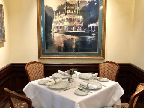 Table for Four, Blue and Brown Chairs, White Table Cloth, and Large Painting of Steam Ship