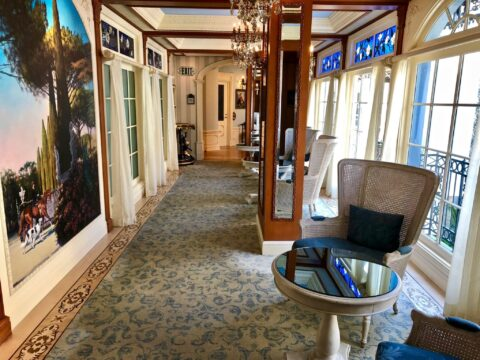 Hallway with Blue and Grey Carpet, Large Painting, and White Walls