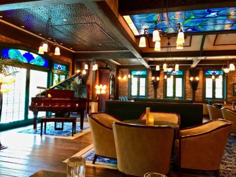 Piano Bar, Blue and Green Stain Glass Windows and Ceiling, Brown Leather Seating with Dim Lighting