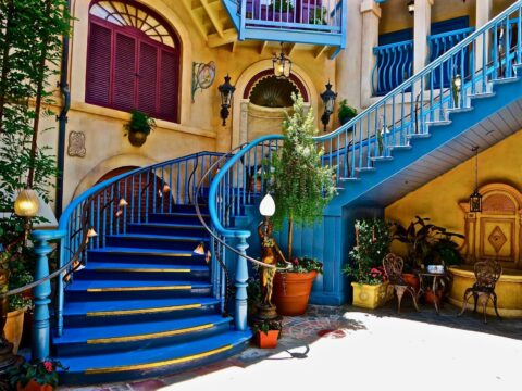 Yellow and Creme Walls, Large Spiral Blue Staircase and Green Foliage at The Court of Angles