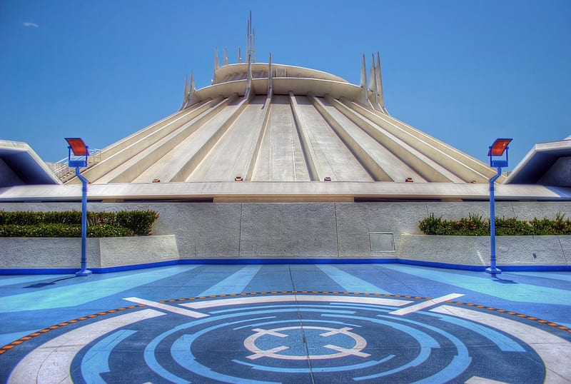 Blue and White Space Mountain Logo on Ground, White/Grey Cylinder Shaped Space Mountain Building
