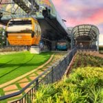 Yellow Disney Skyliner Gondola, Green Bushes and Foliage, Grey Architectural Structure