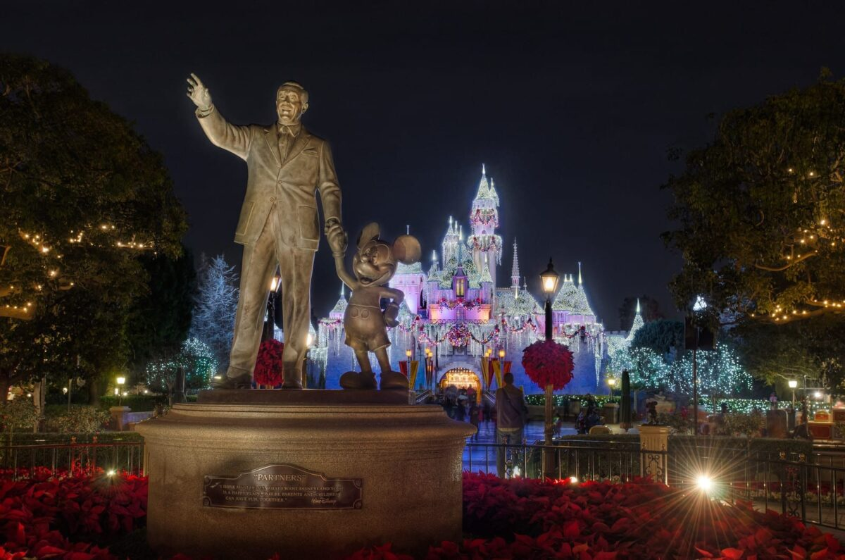 Walt and Mickey statue in front of Disneyland castle decorated for the holidays