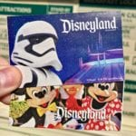 Guest holding two Disneyland tickets with Storm Troopers and Mickey, Goofy, and Minnie