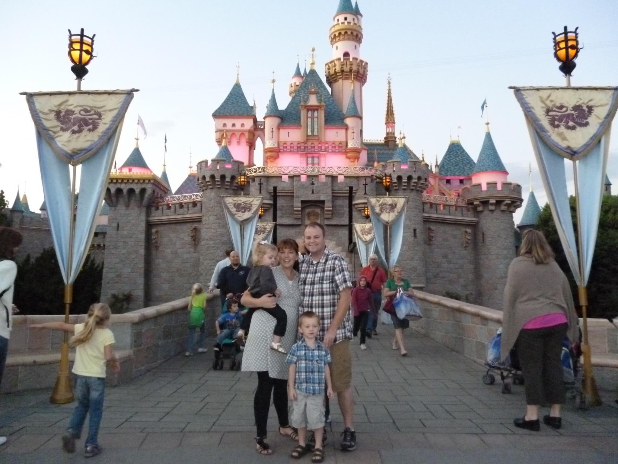 Family smiling in front of Sleeping Beauty's Castle