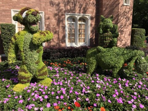 Moss Tigger, Piglet, and Eeyore sculptures in bed of green and purple flowers