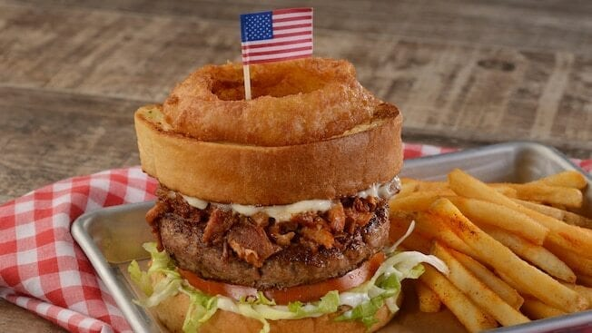Cheeseburger with lettuce, tomato, bacon, sauce, and an onion ring