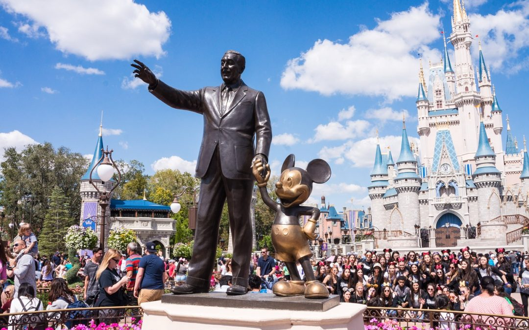 Statue of Walt and Mickey with large crowd in front of Cinderella's Castle