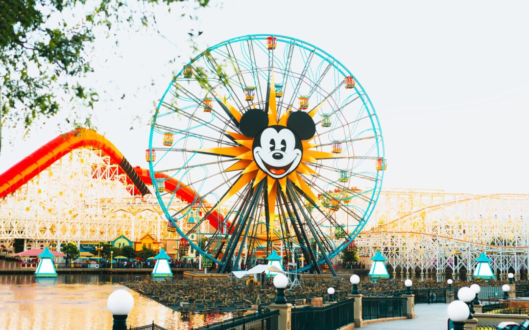 Blue and yellow ferris wheel with mickey mouse on it.