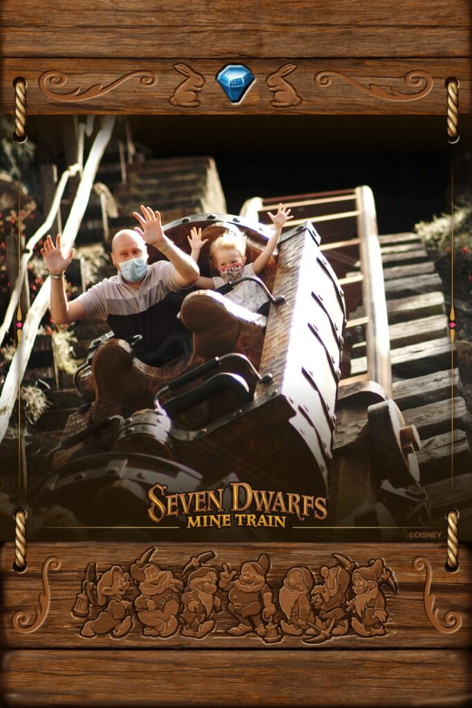 Adult and child riding several dwarfs mine train ride