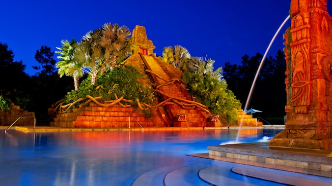 Pool with Aztec pyramids and waterfalls at night