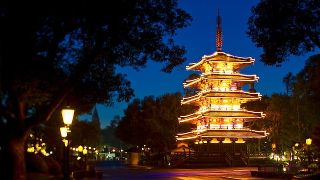 Japanese tower surrounded by trees at night