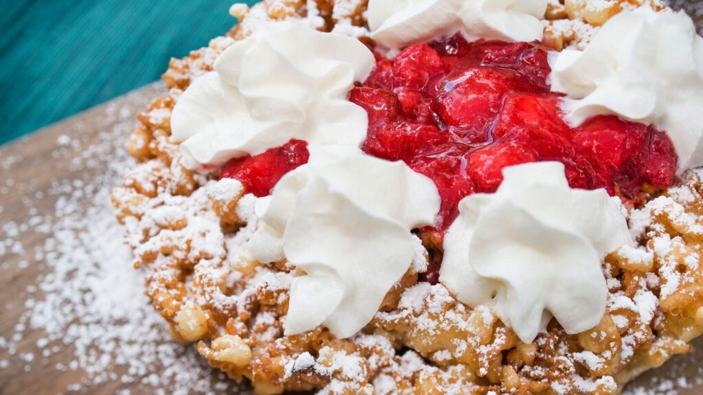 Funnel cake with whipped cream and strawberries