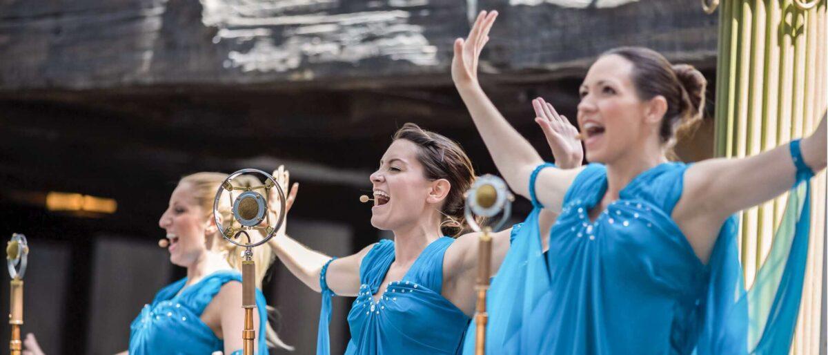 Three women singing on stage