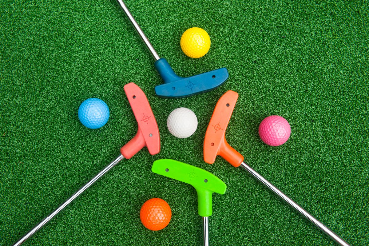 Golf putters and balls one green